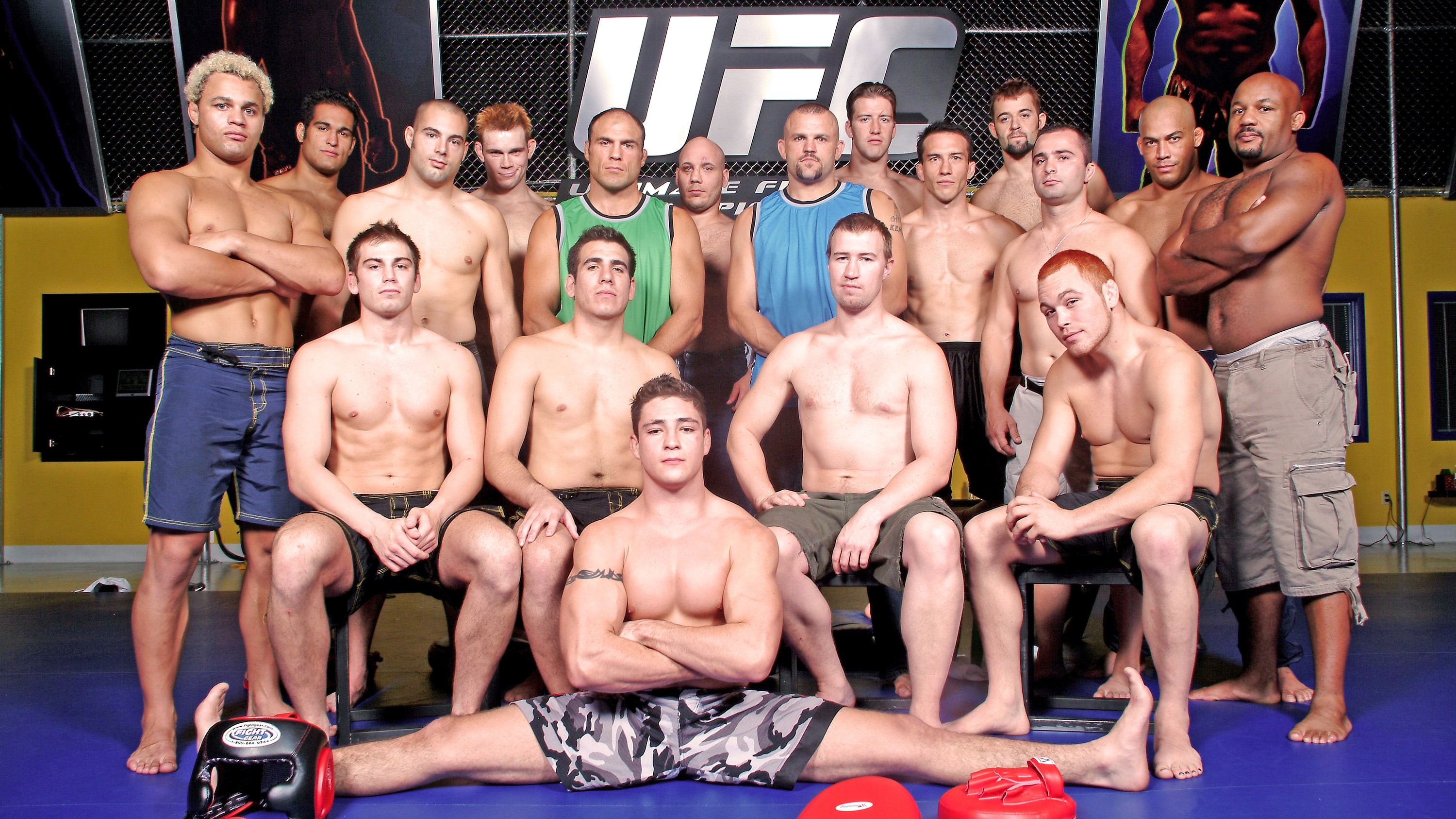 The cast of the original Ultimate Fighter season pose for a photo with coaches Randy Couture and Chuck Liddell.