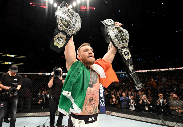 Conor McGregor celebrates with both of his belts after defeating Eddie Alvarez at UFC 205