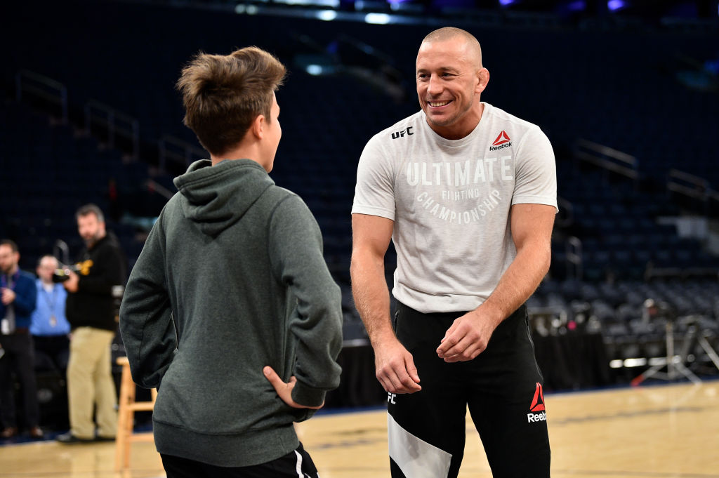 NEW YORK, NY - NOV. 01:  Georges St-Pierre interacts with a fan as he holds an open workout session for fans and media inside Madison Square Garden. (Photo by Jeff Bottari/Zuffa LLC)