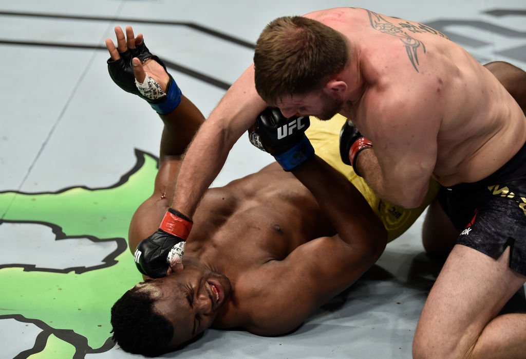 Stipe Miocic punches Francis Ngannou during their heavyweight title fight at UFC 220