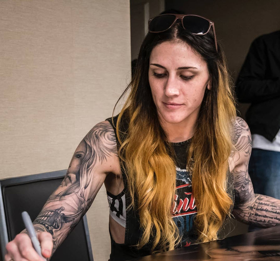 Megan Anderson signs posters at UFC 225 check-ins in Chicago.