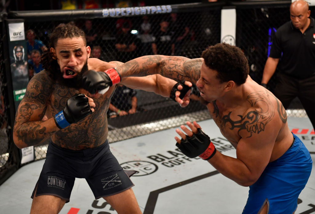 Greg Hardy punches Austen Lane in their heavyweight bout during Dana White's Tuesday Night Contender Series at the TUF Gym on June 12, 2018 in Las Vegas, Nevada. (Photo by Jeff Bottari/DWTNCS LLC)