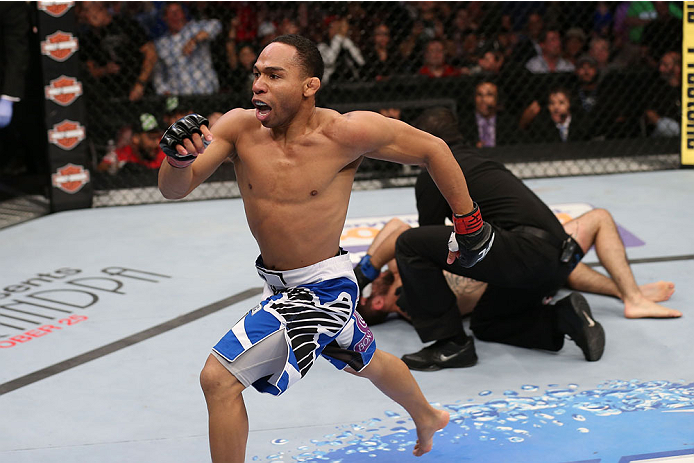 HOUSTON, TEXAS - OCTOBER 19: (L-R) John Dodson runs to the side of the Octagon after defeating Darrell Montague by knockout in their UFC flyweight bout at the Toyota Center on October 19, 2013 in Houston, Texas. (Photo by Nick Laham/Zuffa LLC/Zuffa LLC via Getty Images)