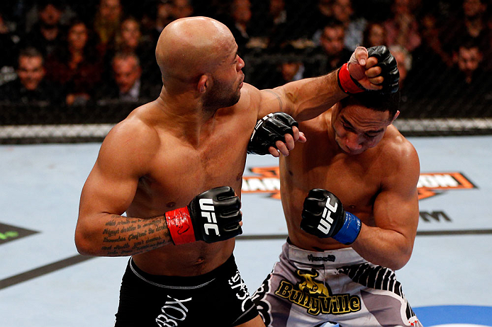 Demetrious Johnson (L) punches John Dodson (R) during their Flyweight Championship Bout part of UFC on FOX at United Center on January 26, 2013 in Chicago (Photo by Josh Hedges/Zuffa LLC).