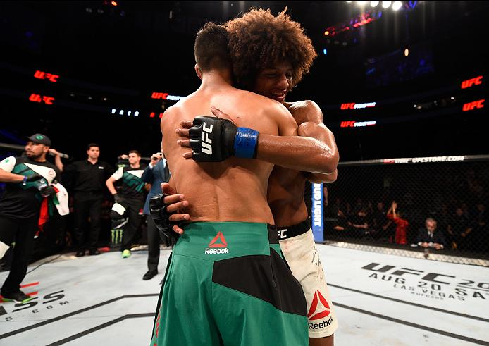SALT LAKE CITY, UT - AUGUST 06:  (L-R) Yair Rodriguez of Mexico and Alex Caceres hug after their featherweight bout during the UFC Fight Night event at Vivint Smart Home Arena on August 6, 2016 in Salt Lake City, Utah. (Photo by Jeff Bottari/Zuffa LLC/Zuf