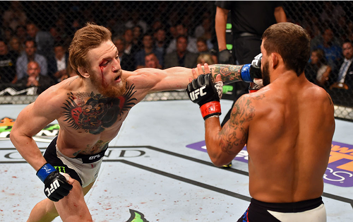 Conor McGregor punches Chad Mendes in their UFC interim featherweight title fight during the UFC 189 event inside MGM Grand Garden Arena on July 11, 2015 in Las Vegas, Nevada. (Photo by Josh Hedges/Zuffa LLC)