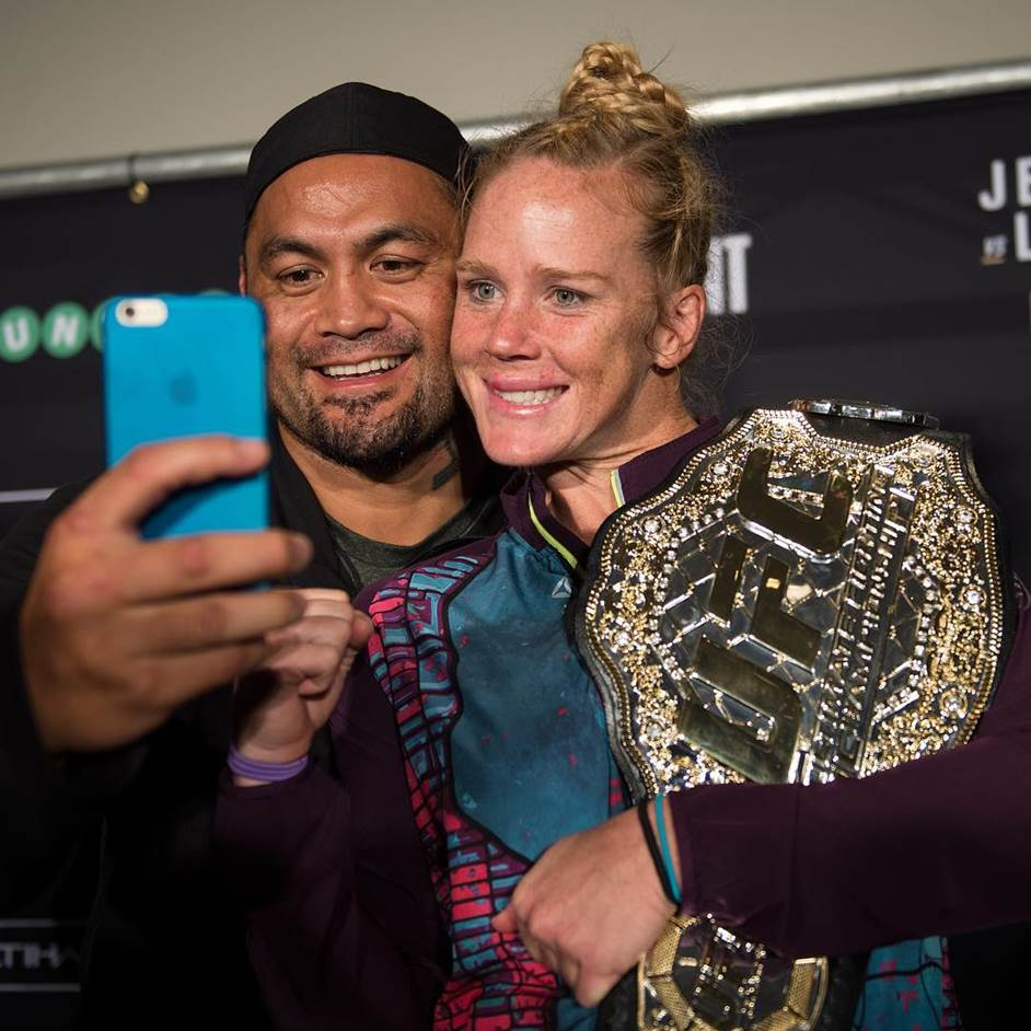 UFC women's bantamweight champion Holly Holm poses for a photo at the UFC 190 post fight press conference with heavyweight Mark Hunt.