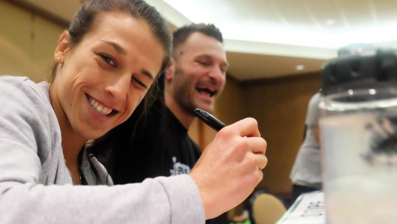DALLAS, TX - MAY 9, 2017: UFC strawweight champion Joanna Jedrzejczyk poses for a photo while signing the official UFC 211 fight posters next to UFC heavyweight champion Stipe Miocic. (Photo by Juan Cardenas/Zuffa LLC)
