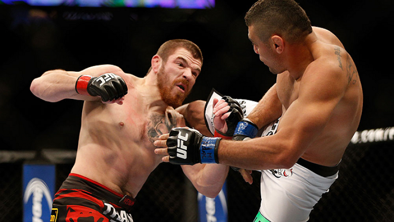 LAS VEGAS, NV - DECEMBER 28:  (L-R) Jim Miller punches Fabricio Camoes in their lightweight bout during the UFC 168 event at the MGM Grand Garden Arena on December 28, 2013 in Las Vegas, Nevada. (Photo by Josh Hedges/Zuffa LLC/Zuffa LLC via Getty Images)