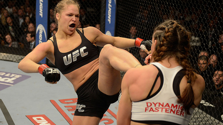 LAS VEGAS, NV - DECEMBER 28:  (L-R) Ronda Rousey kicks Miesha Tate in their UFC women's bantamweight championship bout during the UFC 168 event at the MGM Grand Garden Arena on December 28, 2013 in Las Vegas, Nevada. (Photo by Donald Miralle/Zuffa LLC/Zuf
