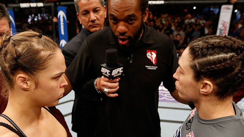 LAS VEGAS, NV - FEBRUARY 22:  Ronda Rousey (left) and Sara McMann (right) listen to instructions from referee Herb Dean (center) before their women's bantamweight championship bout during UFC 170 inside the Mandalay Bay Events Center on February 22, 2014