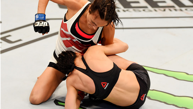 MELBOURNE, AUSTRALIA - NOVEMBER 15: Valerie Letourneau works from the top as she punches Joanna Jedrzejczyk (B) in their UFC women's strawweight championship bout during the UFC 193 event at Etihad Stadium on November 15, 2015 in Melbourne, Australia.  (P
