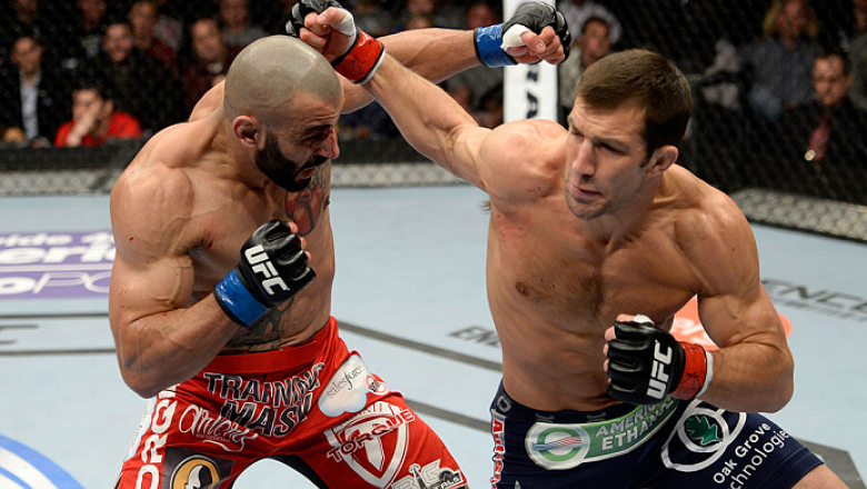 DULUTH, GA - JANUARY 15:  (R-L) Luke Rockhold punches Costas Philippou in their middleweight fight during the UFC Fight Night event inside The Arena at Gwinnett Center on January 15, 2014 in Duluth, Georgia.  (Photo by Jeff Bottari/Zuffa LLC/Zuffa LLC via