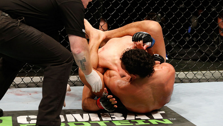 AUCKLAND, NEW ZEALAND - JUNE 28:  (R-L) Charles Oliveira secures a guillotine choke submission against Hatsu Hioki in their featherweight fight during the UFC Fight Night event at Vector Arena on June 28, 2014 in Auckland, New Zealand.  (Photo by Josh Hed