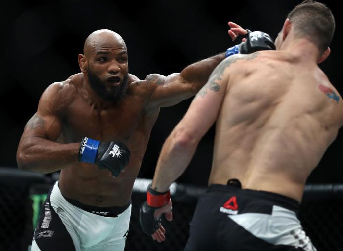 Yoel Romero punches Chris Weidman in their middleweight bout during the UFC 205 event at Madison Square Garden on November 12, 2016 in New York City.