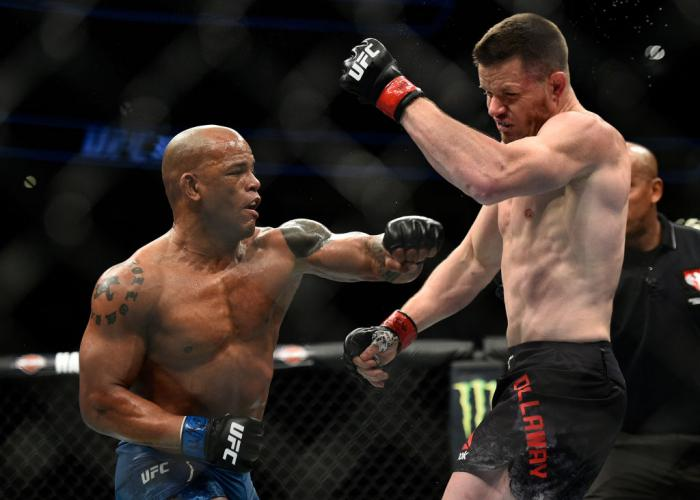 LAS VEGAS, NV - MARCH 03:   (L-R) Hector Lombard of Cuba lands an illegal punch after the end of round one against CB Dollaway in their middleweight bout during the UFC 222 event inside T-Mobile Arena on March 3, 2018 in Las Vegas, Nevada. (Photo by Brand