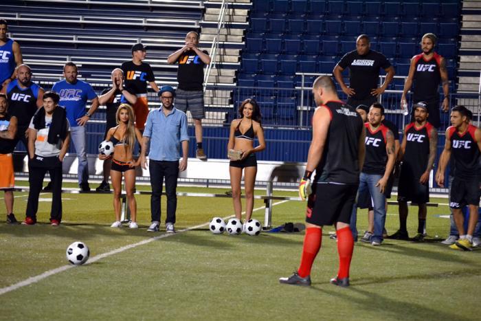 Cain Velásquez se prepara para tirar e intentar penetrar la portería defendida por Fabricio Werdum, mientras ambos equipos observan