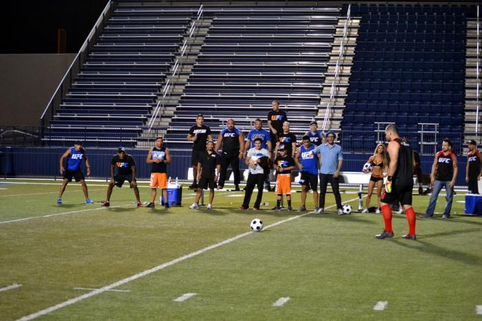 Cain Velásquez se apresta a pegarle al balón mientras ambos equipos lo observan