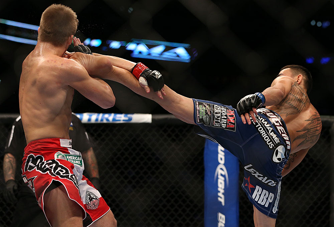 DENVER, CO - AUGUST 11:  (R-L) Max Holloway kicks Justin Lawrence during their featherweight bout at UFC 150 inside Pepsi Center on August 11, 2012 in Denver, Colorado. (Photo by Josh Hedges/Zuffa LLC/Zuffa LLC via Getty Images)