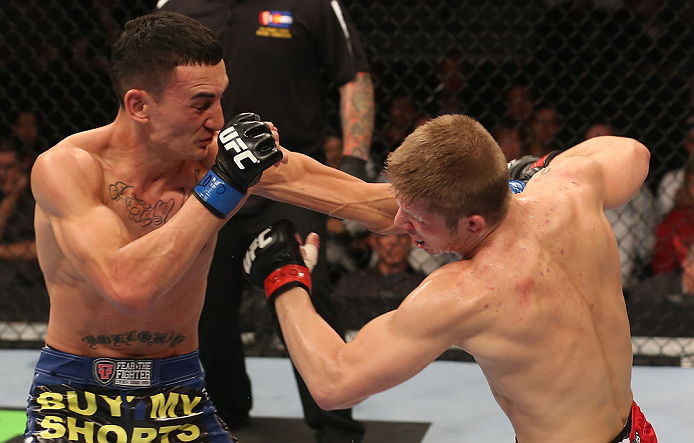 DENVER, CO - AUGUST 11:  (L-R) Max Holloway punches Justin Lawrence during their featherweight bout at UFC 150 inside Pepsi Center on August 11, 2012 in Denver, Colorado. (Photo by Nick Laham/Zuffa LLC/Zuffa LLC via Getty Images)