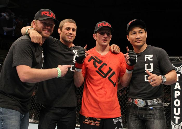 OMAHA, NE - FEBRUARY 15:  TJ Dillashaw (orange shirt) poses for a photo with his team after defeating Walel Watson during the UFC on FUEL TV event at Omaha Civic Auditorium on February 15, 2012 in Omaha, Nebraska.  (Photo by Josh Hedges/Zuffa LLC/Zuffa LL