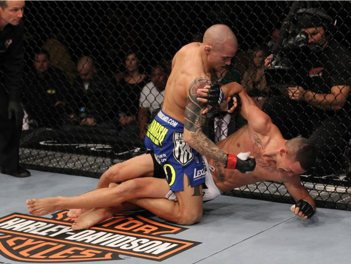 LAS VEGAS, NV - FEBRUARY 04:  Dustin Poirier (blue shorts) delivers punches to Max Holloway from the mount during the UFC 143 event at Mandalay Bay Events Center on February 4, 2012 in Las Vegas, Nevada.  (Photo by Nick Laham/Zuffa LLC/Zuffa LLC via Getty