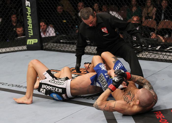 LAS VEGAS, NV - FEBRUARY 04:  Dustin Poirier (right) attempts to submit Max Holloway as referee Steve Mazzagatti looks on during the UFC 143 event at Mandalay Bay Events Center on February 4, 2012 in Las Vegas, Nevada.  (Photo by Nick Laham/Zuffa LLC/Zuff