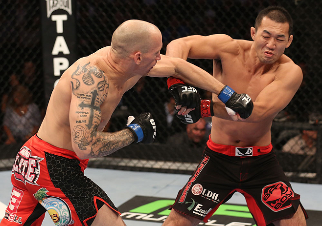 DENVER, CO - AUGUST 11:  (L-R) Buddy Roberts punches Yushin Okami during their middleweight bout at UFC 150 inside Pepsi Center on August 11, 2012 in Denver, Colorado. (Photo by Nick Laham/Zuffa LLC/Zuffa LLC via Getty Images)