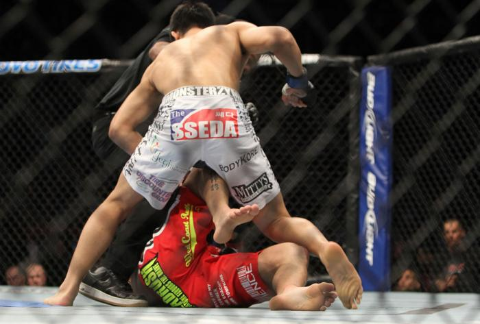 """TORONTO, ON - DECEMBER 10:  """"The Korean Zombie"""" Chan Sung Jung (white shorts) defeats Mark Hominick by knockout during the UFC 140 event at Air Canada Centre on December 10, 2011 in Toronto, Ontario, Canada.  (Photo by Josh Hedges/Zuffa LLC/Zuffa LLC via"""