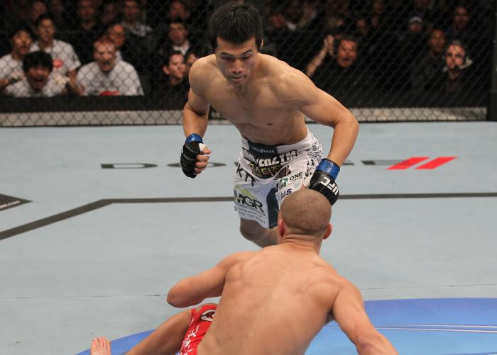 """TORONTO, ON - DECEMBER 10:  (L-R) """"The Korean Zombie"""" Chan Sung Jung rushes in to finish Mark Hominick after knocking him down with a punch during the UFC 140 event at Air Canada Centre on December 10, 2011 in Toronto, Ontario, Canada.  (Photo by Nick Lah"""
