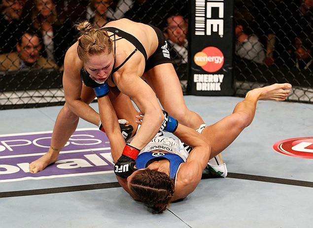 ANAHEIM, CA - FEBRUARY 23:  Ronda Rousey (top) punches Liz Carmouche in their women's bantamweight title fight during UFC 157 at Honda Center on February 23, 2013 in Anaheim, California.  (Photo by Josh Hedges/Zuffa LLC/Zuffa LLC via Getty Images) *** Loc