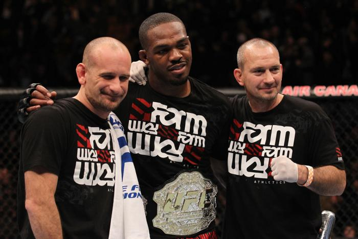 """TORONTO, ON - DECEMBER 10:  UFC Light Heavyweight Champion Jon """"Bones"""" Jones poses for a photo with his trainers Greg Jackson (L) and Mike Winklejohn (R) after defeating Lyoto Machida during the UFC 140 event at Air Canada Centre on December 10, 2011 in T"""