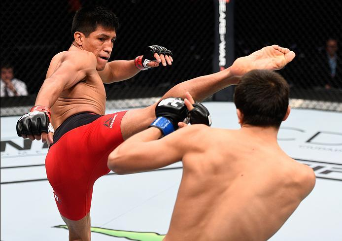 MEXICO CITY, MEXICO - NOVEMBER 05:  (L-R) Enrique Barzola of Peru kicks Chris Avila of the United States in their featherweight bout during the UFC Fight Night event at Arena Ciudad de Mexico on November 5, 2016 in Mexico City, Mexico. (Photo by Jeff Bott