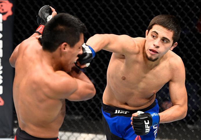 MEXICO CITY, MEXICO - NOVEMBER 05:  (R-L) Chris Avila of the United States punches Enrique Barzola of Peru in their featherweight bout during the UFC Fight Night event at Arena Ciudad de Mexico on November 5, 2016 in Mexico City, Mexico. (Photo by Jeff Bo
