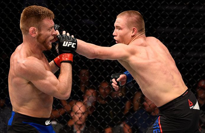 SIOUX FALLS, SD - JULY 13:   (R-L) Cody Pfister punches Scott Holtzman in their lightweight bout during the UFC Fight Night event on July 13, 2016 at Denny Sanford Premier Center in Sioux Falls, South Dakota. (Photo by Jeff Bottari/Zuffa LLC/Zuffa LLC via