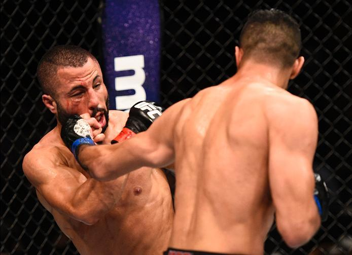 LAS VEGAS, NV - JULY 07:   (R-L) Mehdi Baghdad of France punches John Makdessi of Canada in their lightweight bout during the UFC Fight Night event inside the MGM Grand Garden Arena on July 7, 2016 in Las Vegas, Nevada. (Photo by Jeff Bottari/Zuffa LLC/Zu