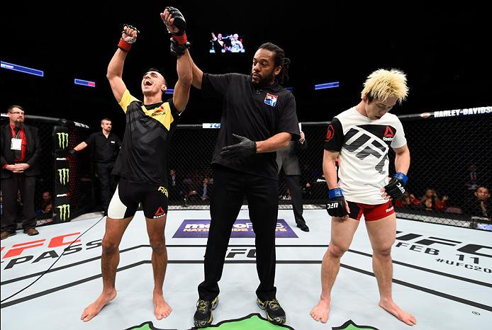 HOUSTON, TX - FEBRUARY 04:  (L-R) Ricardo Ramos of Brazil celebrates his victory over Michinori Tanaka of Japan in their bantamweight bout during the UFC Fight Night event at the Toyota Center on February 4, 2017 in Houston, Texas. (Photo by Jeff Bottari/