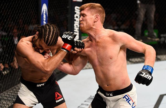 OTTAWA, ON - JUNE 18:   (R-L) Sam Alvey of the United States punches Elias Theodorou of Canada in their middleweight bout during the UFC Fight Night event inside the TD Place Arena on June 18, 2016 in Ottawa, Ontario, Canada. (Photo by Jeff Bottari/Zuffa