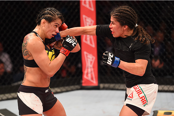 RIO DE JANEIRO, BRAZIL - AUGUST 01:  (R-L) Jessica Aguilar of the United States punches Claudia Gadelha of Brazil in their women's strawweight bout during the UFC 190 event inside HSBC Arena on August 1, 2015 in Rio de Janeiro, Brazil.  (Photo by Josh Hed