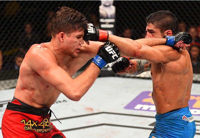 NEW ORLEANS, LA - JUNE 06:   (R-L) Thiago Tavares exchanges punches with Brian Ortega in their featherweight bout during the UFC event at the Smoothie King Center on June 6, 2015 in New Orleans, Louisiana. (Photo by Josh Hedges/Zuffa LLC/Zuffa LLC via Get