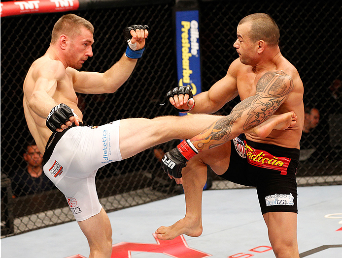 BRASILIA, BRAZIL - SEPTEMBER 13: (L-R) Piotr Hallmann of Poland kicks Gleison Tibau of Brazil in their lightweight bout during the UFC Fight Night event inside Nilson Nelson Gymnasium on September 13, 2014 in Brasilia, Brazil. (Photo by Josh Hedges/Zuffa