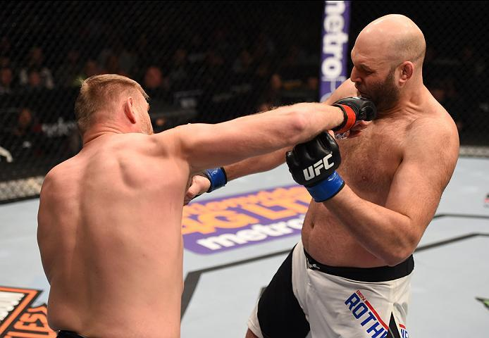 NEWARK, NJ - JANUARY 30:  (L-R) Josh Barnett  punches Ben Rothwell in their heavyweight bout during the UFC Fight Night event at the Prudential Center on January 30, 2016 in Newark, New Jersey. (Photo by Josh Hedges/Zuffa LLC/Zuffa LLC via Getty Images)