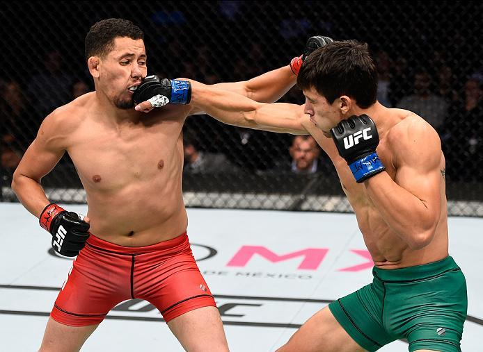 MEXICO CITY, MEXICO - NOVEMBER 05:  (R-L) Claudio Puelles of Peru punches Martin Bravo Flores of Mexico in their lightweight bout during the UFC Fight Night event at Arena Ciudad de Mexico on November 5, 2016 in Mexico City, Mexico. (Photo by Jeff Bottari