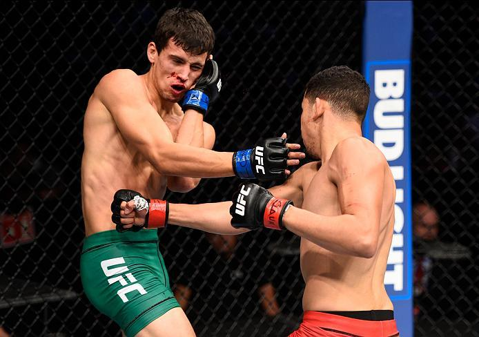 MEXICO CITY, MEXICO - NOVEMBER 05:  (R-L) Martin Bravo Flores of Mexico punches Claudio Puelles of Peru in their lightweight bout during the UFC Fight Night event at Arena Ciudad de Mexico on November 5, 2016 in Mexico City, Mexico. (Photo by Jeff Bottari