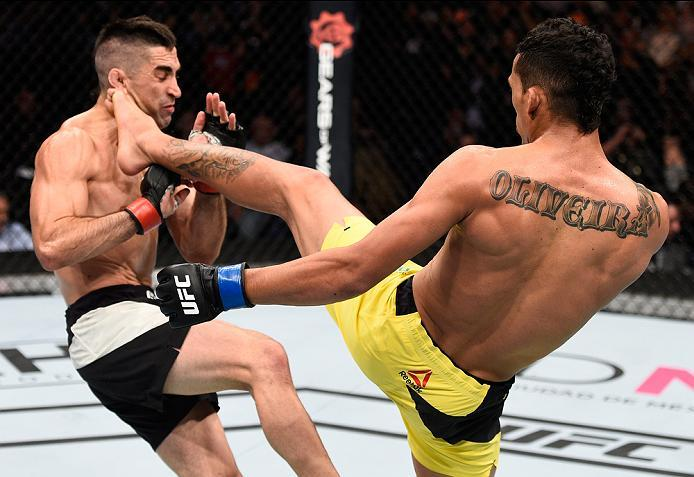 MEXICO CITY, MEXICO - NOVEMBER 05:  (R-L) Charles Oliveira of Brazil kicks Ricardo Lamas of the United States in their featherweight bout during the UFC Fight Night event at Arena Ciudad de Mexico on November 5, 2016 in Mexico City, Mexico. (Photo by Jeff