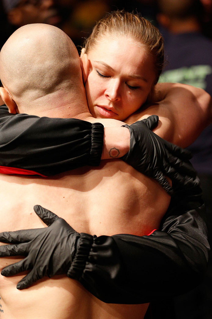 BOSTON, MA - AUGUST 17:  (R-L) UFC women's bantamweight champion Ronda Rousey supports teammate Manny Gamburyan during his UFC featherweight bout against Cole Miller at TD Garden on August 17, 2013 in Boston, Massachusetts. (Photo by Josh Hedges/Zuffa LLC