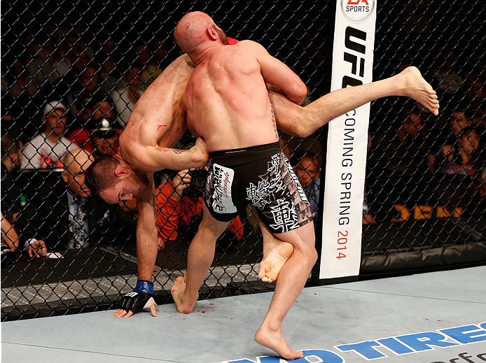 BOSTON, MA - AUGUST 17:  (R-L) Manny Gamburyan takes down Cole Miller in their UFC featherweight bout at TD Garden on August 17, 2013 in Boston, Massachusetts. (Photo by Josh Hedges/Zuffa LLC/Zuffa LLC via Getty Images)