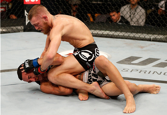 BOSTON, MA - AUGUST 17:  (R-L) Conor McGregor punches Max Holloway in their UFC featherweight bout at TD Garden on August 17, 2013 in Boston, Massachusetts. (Photo by Josh Hedges/Zuffa LLC/Zuffa LLC via Getty Images)