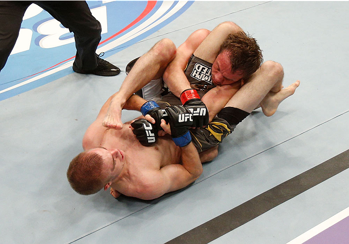 BOSTON, MA - AUGUST 17:  Michael McDonald (bottom) secures a triangle choke submission against Brad Pickett in their UFC bantamweight bout at TD Garden on August 17, 2013 in Boston, Massachusetts. (Photo by Josh Hedges/Zuffa LLC/Zuffa LLC via Getty Images