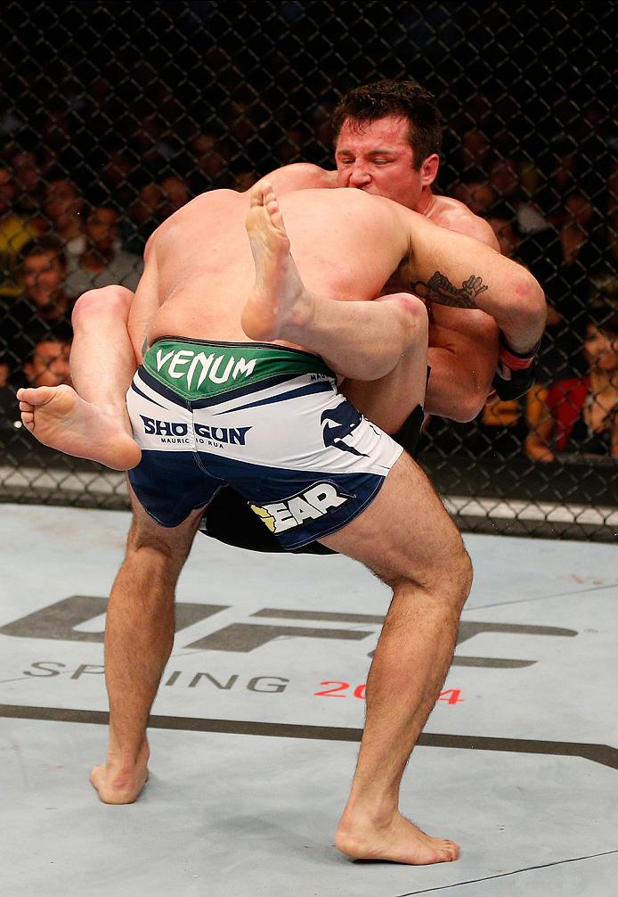 "BOSTON, MA - AUGUST 17:  (R-L) Chael Sonnen secures a guillotine choke submission against Mauricio ""Shogun"" Rua in their UFC light heavyweight bout at TD Garden on August 17, 2013 in Boston, Massachusetts. (Photo by Josh Hedges/Zuffa LLC/Zuffa LLC via Get"